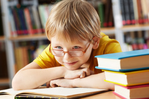 Portrait of  boy with open book in library