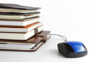 Stack of books and mouse. Online education and business concept